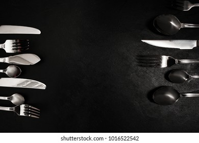 Silver cutlery on black background. food etiquette concept