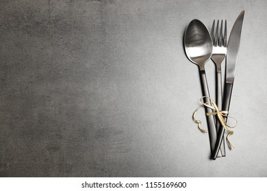 Silver cutlery on gray background, top view. Table setting