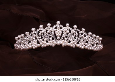 silver diadem with diamonds and pearls isolated on the fabric