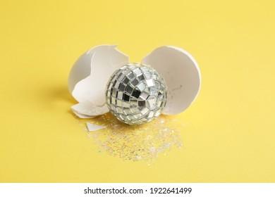Silver disco ball, broken eggshell and glitter sprinkles on yellow background