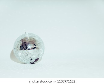 Silver disco ball on a white background. Light reflects on the floor.
