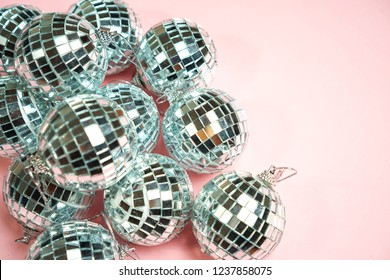 Silver disco balls for decoration party on pastel pink gradient background. Winter New Years Eve party holiday concept. top view, flat lay close up mirror ball. Frame with room for copy.