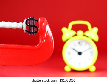 A silver Dollar symbol placed in a red clamp with a red background, with a yellow alarm clock in the background indicating the pressure on the pound sterling.