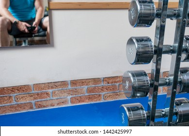silver dumbbells are in the foreground and a mirror with the mirror image of an athlete hangs on the wall