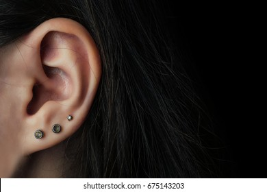 Silver Earring on the girl's ear close-up on a black background