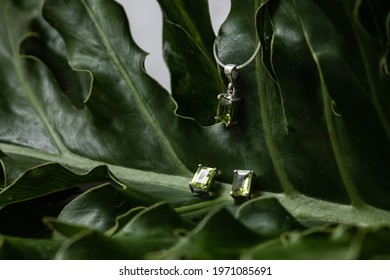 Silver and emerald set jewelry with pendant, chain and earrings. Rectangle greenstone. Leaf background.