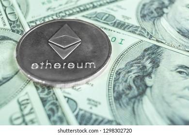 Silver Ethereum on hundred dollars bills. Close-up, macro shot.