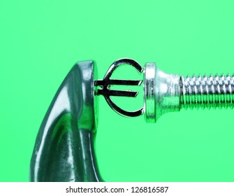 A silver Euro symbol placed in a clamp with a light green background, indicating the pressure is on the currency.