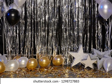Silver festive background with balloons, stars and confetti illuminated by colored lanterns.