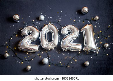 Silver foil balloons made numbers 2021 on black background with garland. Holiday party decoration. Happy new year celebration, congratulation concept.