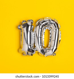 Silver foil number 10 celebration balloon on a bright yellow background
