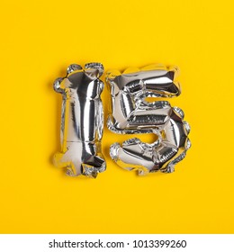 Silver foil number 15 celebration balloon on a bright yellow background