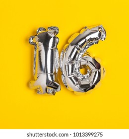 Silver foil number 16 celebration balloon on a bright yellow background
