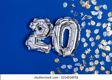 Silver Foil Number 20 Balloon On A Blue Background With Glitter Gonfetti