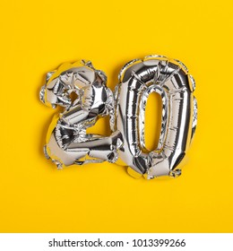 Silver foil number 20 celebration balloon on a bright yellow background