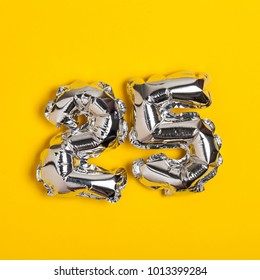 Silver foil number 25 celebration balloon on a bright yellow background