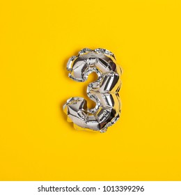 Silver foil number 3 celebration balloon on a bright yellow background