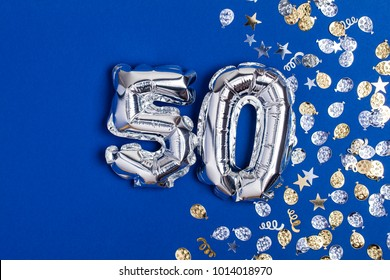 Silver foil number 50 balloon on a blue background with glitter gonfetti