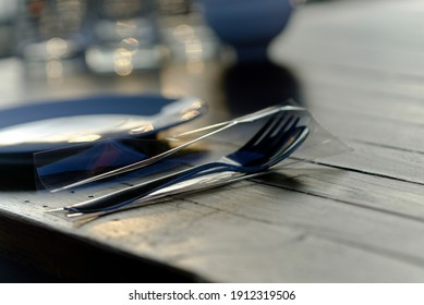 silver folk and spoon lay on the wooden table near the black plate.