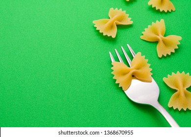 Silver fork with farfalle on a green background with pasta around with copyspace