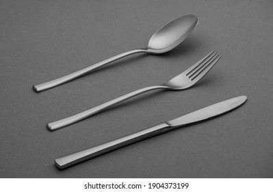Silver fork, knife andd spoon, cutlery set isolated on grey background