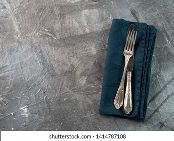 Silver fork and knife on dark green emerald linen napkin over gray textured background table with copy space. Cutlery with copy space, top view or flat lay