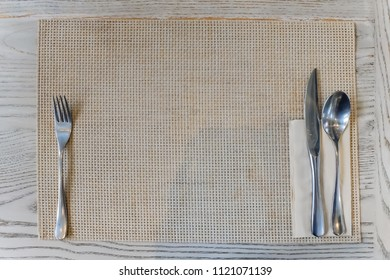 Silver Fork and knife with White Napkin Top View on wooden table background