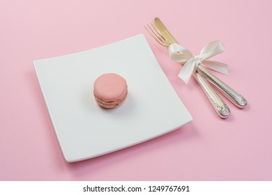 Silver fork and knife with white ribbon and plate with a maracon on pink background