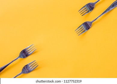 silver Forks on bright yellow background, creative layout,Kitchen texture, top view Flat lay.Food concept.mock up,flatware frame with copy space isolated on yellow.table setting theme template with