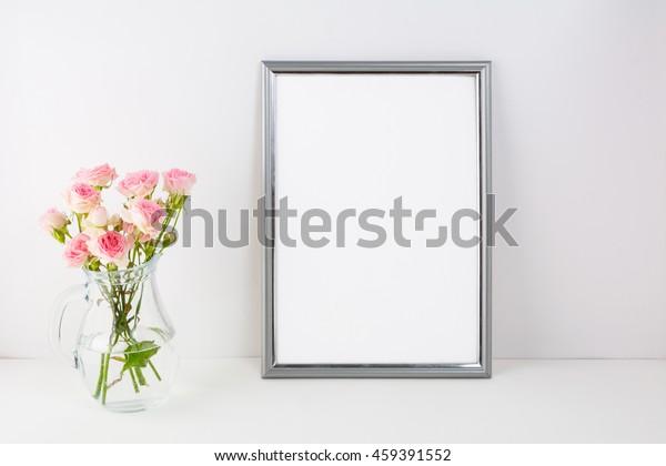 Der silberne Rahmen ist mit rosafarbenen Rosen bespannt. Porträt oder Plakat leere weiße Rahmen Vorlage für Präsentationen.