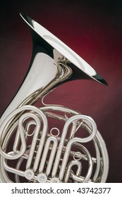 A silver French horn isolated against a spotlight red background in the vertical format.