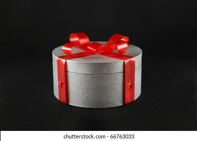 Silver gift box with red ribbon - black background