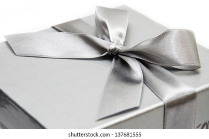silver gift box with ribbon over white