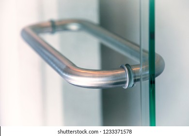 Silver Glass door handle of a glass partition shower unit. Bathroom glass door detail with bath tub in the background. Selective focus and soft light effect added.