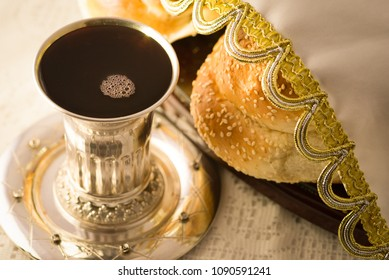 A silver goblet filled with grape juice alongside covered bread for the Shabbat (Sabbath) blessing.