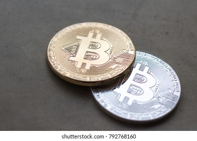 Silver and gold coins of bitcoin on the grey background.