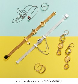 Silver and gold jewelry on minimal yellow and blue background. Rings, bracelets, earrings and necklace. Top view of fashion luxury woman accessories, jewelry and shopping concept. Flat lay composition