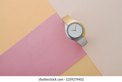 Silver and gold modern wrist watch on pink and peach color paper background top view