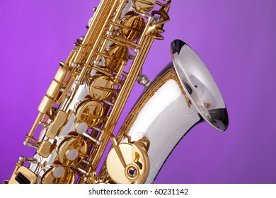 A silver and gold professional alt saxophone isolated against a pink background.