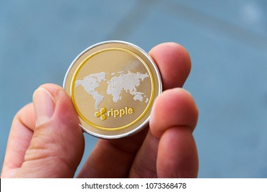 Silver gold ripple coin in hand, cryptocurrency investing concept