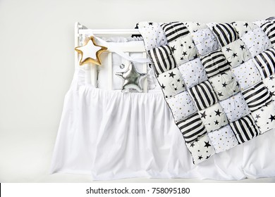 Silver and gold star shaped pillows and patchwork comforter on a white baby cot