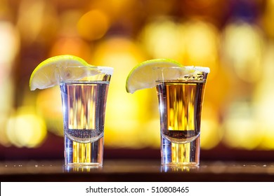 Silver and gold tequila in a glass on a background of bright lights. Traditional Mexican drink.