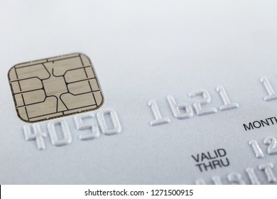 Silver gray smart credit card, PVC EMV, close up with selective focus on embossed numbers, electronic chip, dots pattern on background and white blank copy space on top. Payment, security financial.
