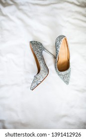 silver grey wedding shoes on white background. trendy bridal high heels. Luxury, glamorous and feminine looks. Beauty and fashion concept.