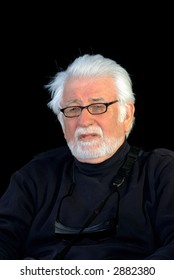 Silver haired man in black on a black background.