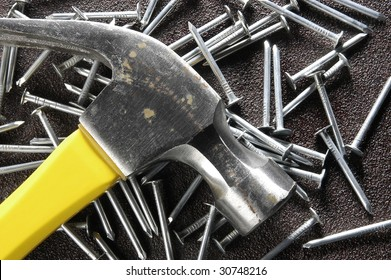 Silver hammer with yellow handle lay on the floor with nails