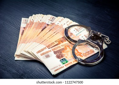 silver handcuffs on many large rubles notes