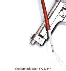 silver handgun  and cigarette in cigarette holder on white background