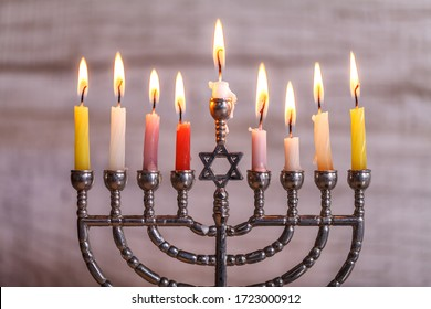 Silver Hanukkah menorah with candles on a light wooden background. Holiday concept