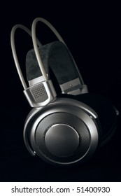 Silver headphones on black background.